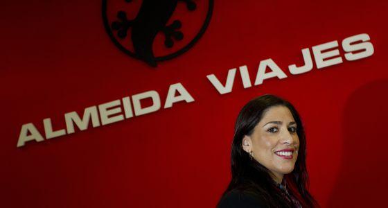 La empresaria Inmaculada Almeida frente a un letrero de su agencia de viajes en Málaga.